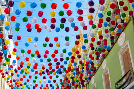 Colorful decoration with paper balls on streets in old part of ancient town Ronda, Andalusia, Spain in summer