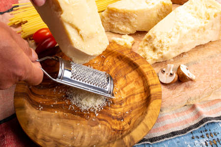 Man cooking with hard italian cheese, grated parmesan or grana padano cheese, hand with cheese grater