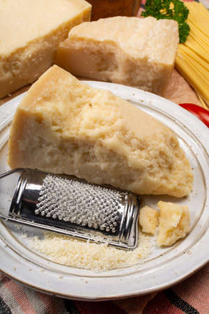 Cooking with hard italian cheese, grated parmesan or grana padano cheese close up