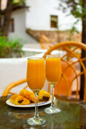 Healthy breakfast with two glasses of freshly squeezed orange juice  served outdoor on glass table
