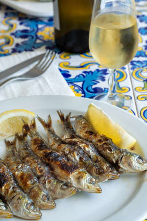Sardines espeto, Malaga style fish on stick barbecue prepared on olive tree firewoods served with glass dry fino sherry wine