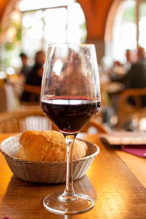One glass ruby red wine served with bread in cafe during dinner with many people