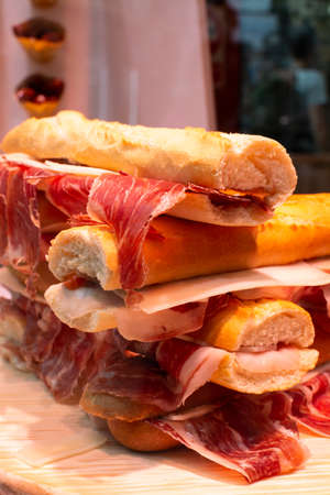 Spanish tapas street food, bocadillo fresh bread with jamon iberico ready to eat