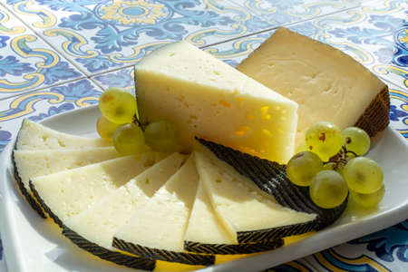 Spanish sheep cheese served with white grapes on andalusian style table