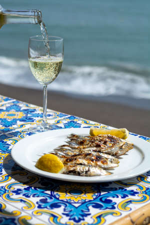 Sardines espeto, Malaga style fish on stick barbecue prepared on olive tree firewoods on beach served with white wine