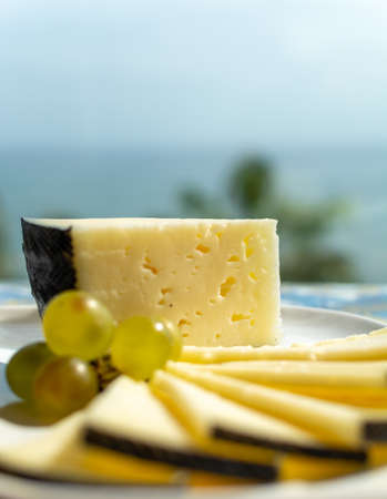 Spanish sheep cheese served with white grapes on andalusian style table outside with sea view