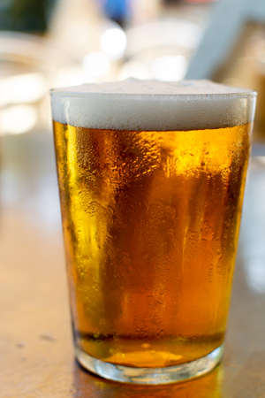 Cold amber color light spanish beer served in glass in outdoor cafe in sunny Andalusia, Spain close up