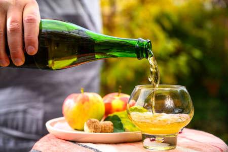 Verser du cidre de pomme français en verre fabriqué à partir de pommes de la nouvelle récolte en plein air dans un verger ensoleillé