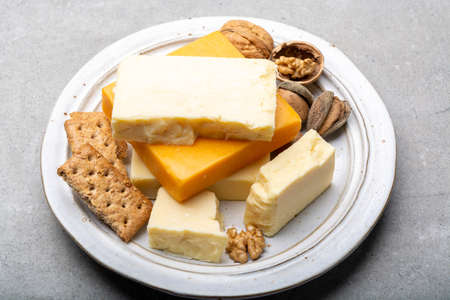 Cheese collection, matured and orange original British cheddar cheese in blocks served with crackers close up Stockfoto