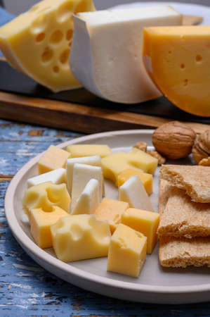 Tasty snacks, cheese blocks from Dutch yellow gouda and white goat hard cheeses and French holes cheese emmentaler close up