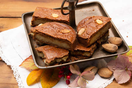 Fresh baked Dutch filled spicy cookies with almonds in autumn colors on dark wooden background close up