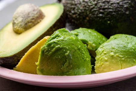 Eating of fresh ripe green organic hass avocado tropical fruit Stockfoto
