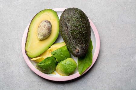 Eating of fresh ripe green organic hass avocado tropical fruit copy space