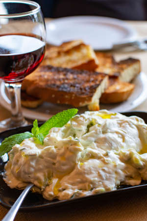Tzatziki, cacik or tarator,  dip or sauce from Southeast Europe and Middle East made of salted strained yogurt mixed with cucumbers, garlic, salt, olive oil, vinegar or lemon juice, and dill, mint, parsley and thyme close up Stock fotó
