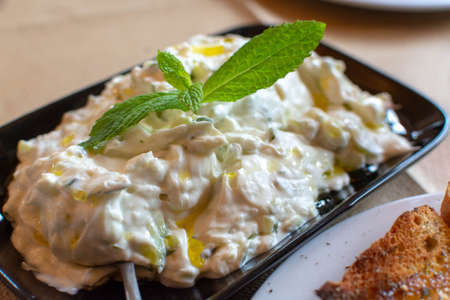 Tzatziki, cacik or tarator,  dip or sauce from Southeast Europe and Middle East made of salted strained yogurt mixed with cucumbers, garlic, salt, olive oil, vinegar or lemon juice, and dill, mint, parsley and thyme close up 免版税图像