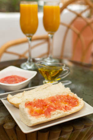 Traditional andalusian breakfast with freshly squeezed orange juice, bread toasts, fresh ground tomatoes sauce and olive oil