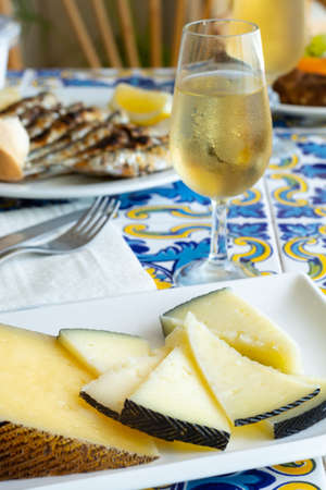 Andalusian food, chees en espeto, Malaga style fish on stick barbecue served with glass dry fino sherry wine