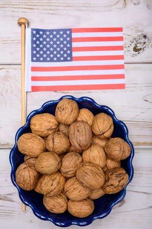 American food concept, new harvest of Californian walnuts  and flag of USA close up