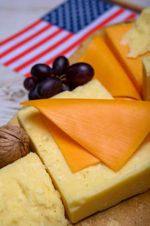 Cheese collection, blocks and slices of yellow and matured american cheddar cheese with flag of USA, american food concept Banco de Imagens