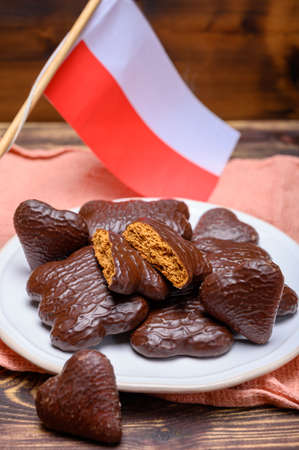 Tasty gingerbread glazed cookies from Torun, Poland and flag of Poland close up Banco de Imagens