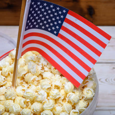 Plastic bucket with tasty sweet popcorn ready to eat and flag of USA