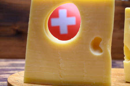 Cheese collection, swiss emmentaler cheese with big holes and flag of Switzerland close up