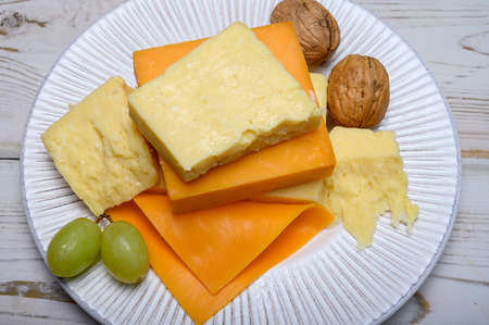Cheese collection, blocks and slices of yellow and matures english cheddar cheese close up