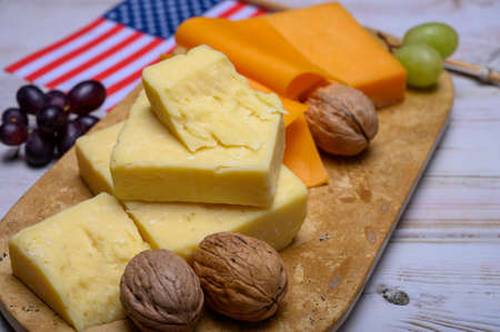 Cheese collection, blocks and slices of yellow and matured american cheddar cheese and Californian walnuts with flag of USA, american food concept