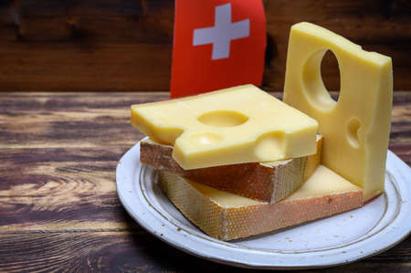 Cheese collection, swiss emmentaler, Gruyere, appenzeller cheeses and flag of Switzerland close up