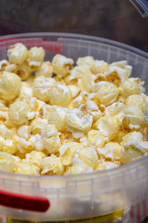 Plastic bucket with tasty sweet popcorn ready to eat