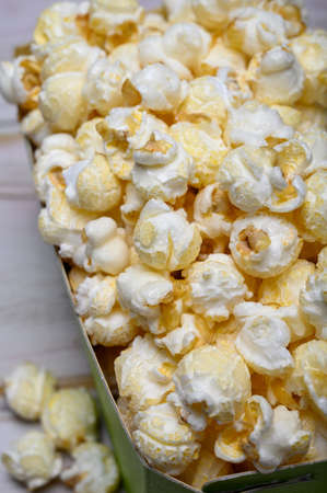 Green paper box with sweet popcorn ready to eat close up