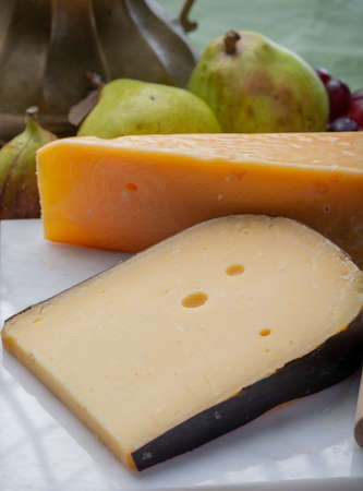 Pieces of aged original Dutch hard cheeses close up served with fresh pears