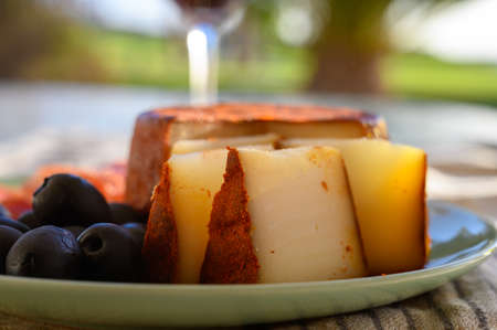 Tastes of Spain, jamon iberian, black olives and manchego cheese with red paprika close up in sun lights