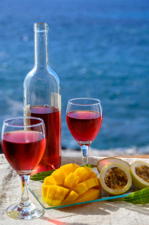 Two glasses of cold rose wine served outdoor with exotic fruits on tropical island La Palma, Canary islands, Spain with beautiful blue ocean view
