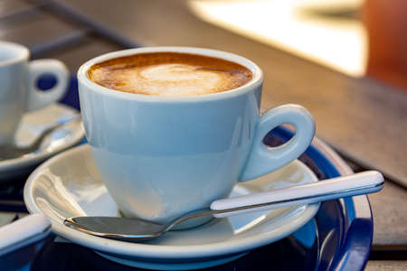 White cup with italian coffee capuccino made from fresh roasted coffee beans and hot milk close up Imagens