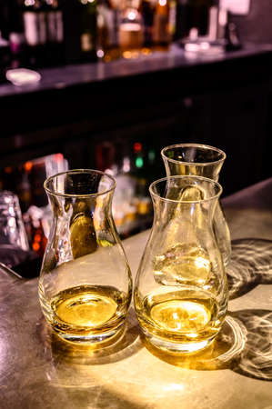 Flight of Scottish whisky, tasting glasses with variety of single malts or blended whiskey spirits on distillery tour in pub in Scotland, UK 免版税图像