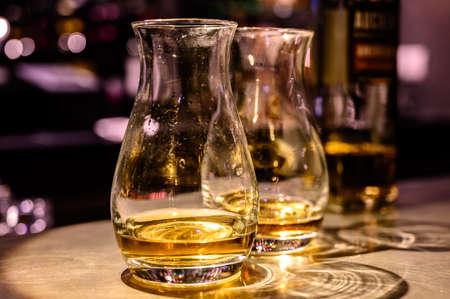 Volo di whisky scozzese, bicchieri da degustazione con varietà di single malt o liquori di whisky miscelati durante il tour della distilleria in un pub in Scozia, Regno Unito Archivio Fotografico