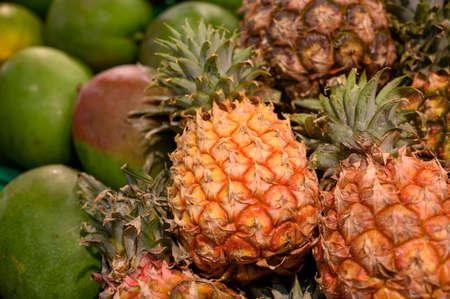 Exotic fruits, fresh ripe sweet pinapples and mango, tropical food background close up