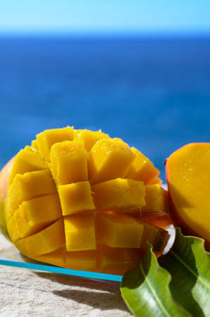 Fresh ripe sweet yellow mango fruit served on glass plate with blue seaview background, close up