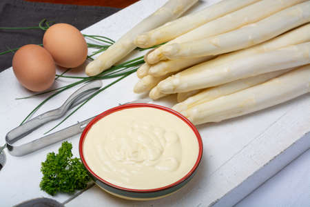 White hollandaise sauce in bowl, traditional sauce for dishes with cooked white asparagus close up