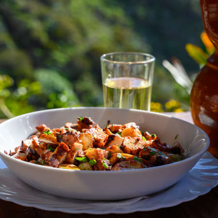 Tastes of Spain, fresh homemade Galician octopus salad with red paprika and parsley served outside on table Banco de Imagens