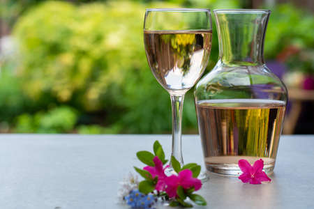 French rose wine served in garden in glass and carafe with colorful spring flowers in sunny day