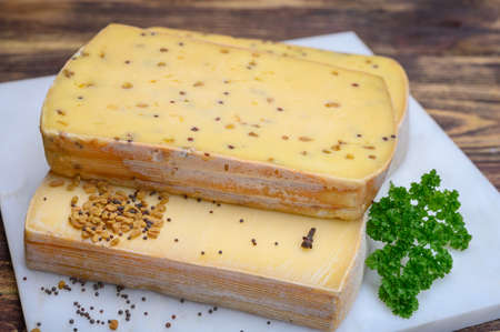 Belgian cheeses from abbey made from cow milk with monks beer, fenugreek and mustard seeds close up Stock Photo