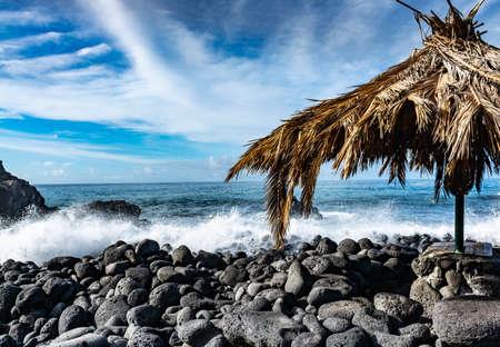 Dangerous ocean stormy waves hits black lava rocks on Playa de la Bombilla, La Palma island, Canary, Spain, bad winter weather conditions