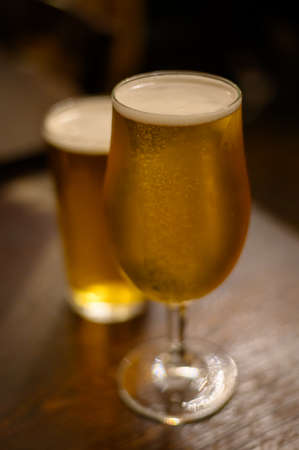 Misty glasses with two pints of cold Scotch ale, pale ale, lager draft beer in English pub close up