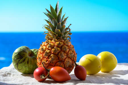 Tropical fruits collection, custard apple or green ripe cherymoia, passion fruit, pineapple, mango, tamarillo exotic fruits on blue sea background in sunny day