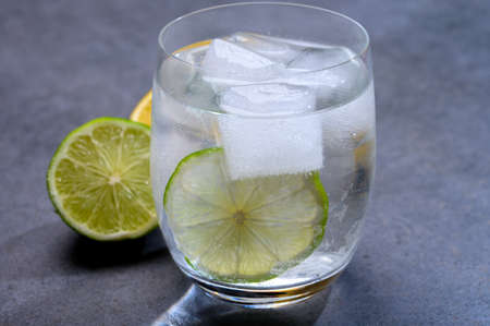 Cold drinking mineral water served in glass with ice cubes and green lime close up
