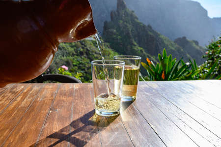 Man pouring white wine from clay jug into glass on terrace with view on green landscapes of small mountain village Masca on Tenerife, Spain in sunny day Banque d'images - 139226571