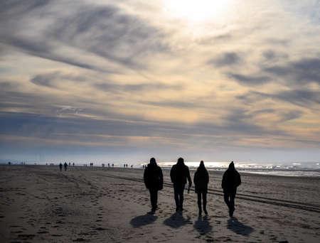 Unidentified peolpe walking on North sea sandy beach during low tide near Castricum aan Zee, winter in Netherlands Stockfoto