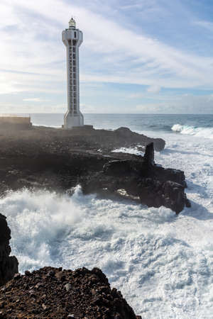 Dangerious ocean stormy waves hits black lava rocks by Faro de las Hoyas, La Palma island, Canary, Spain, bad winter weather conditions